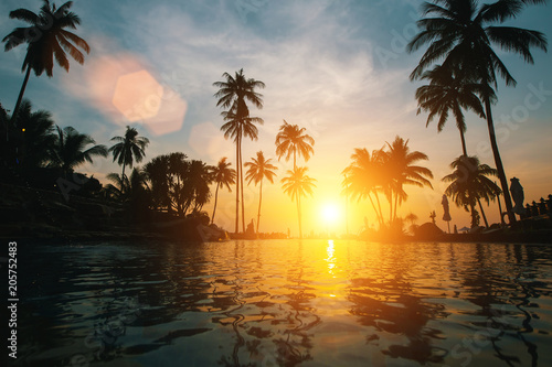 Amazing sunset on tropical beach with silhouettes of palm trees..