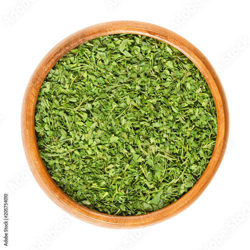Dried parsley in wooden bowl. Also called garden parsley or petersilie. Petroselinum crispum. Green herb, spice and vegetable. Isolated macro food photo close up from above on white background.