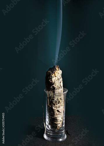 Sage with smoke burning in a glass against a black