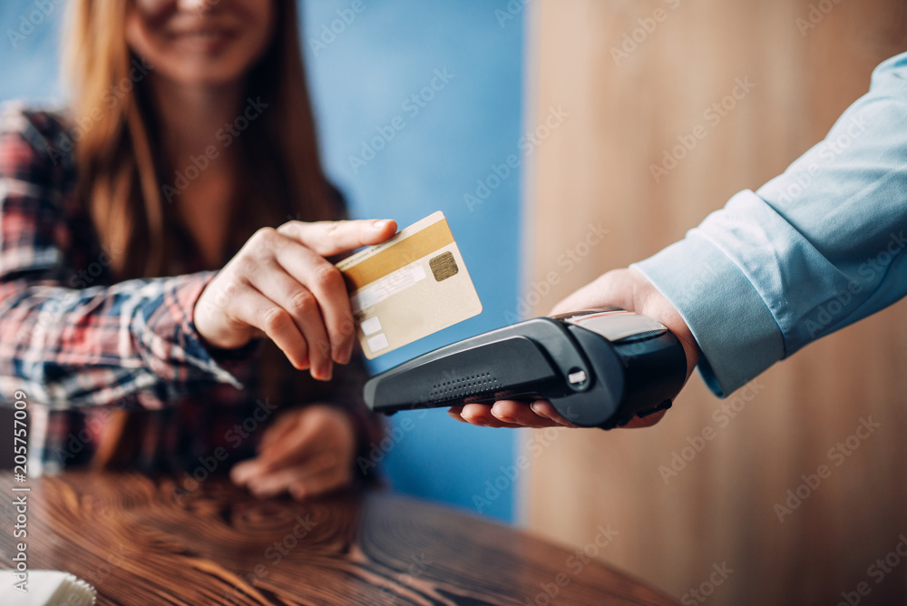 Fototapeta Young woman paying with credit card in cafe