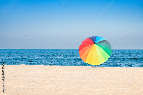 Fotografie, Obraz  Colored umbrella on beach with white sand and blue sky