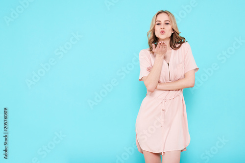 Elegant young attractive woman wearing pale pink summer dress isolated over pastel blue background, blowing a kiss towards camera Fototapeta