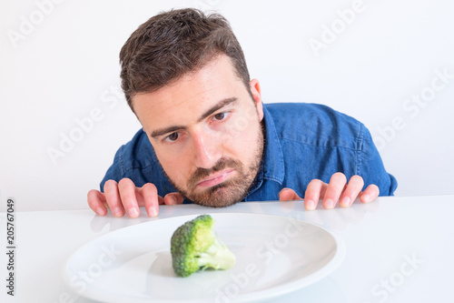 Fotografie, Tablou  Hungry man feeling sad in front of a dish with a cabbage