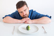 Sad and frustrated man on diet having only vegetables for meal