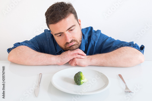 Sad and frustrated man on diet having only vegetables for meal Fotobehang