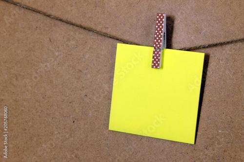 Photo Hoja de papel de color amarillo  (posit), sujeto con una pequeña pinza de color