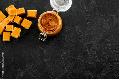 Canvas Prints Bar Caramel sauce in glass jar near caramel cubes on black background top view copy space