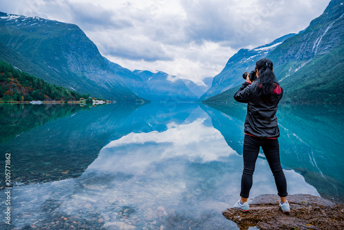 Fototapeta Nature photographer tourist with camera shoots lovatnet lake Beautiful Nature Norway. obraz