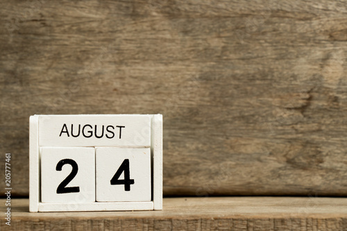 Fényképezés  White block calendar present date 24 and month August on wood background