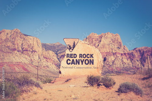 Poster de jardin Parc Naturel Rock boulder sign for Red Rock Canyon in Las Vegas Nevada with mountains in the background