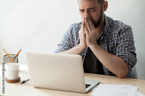 Sick man blowing nose while working at laptop, suffering from congestion and fever Tapéta, Fotótapéta