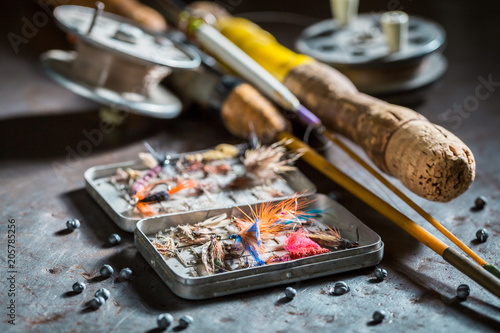 Fotografia, Obraz Fishing tackle with fishing flies and rods on metal table