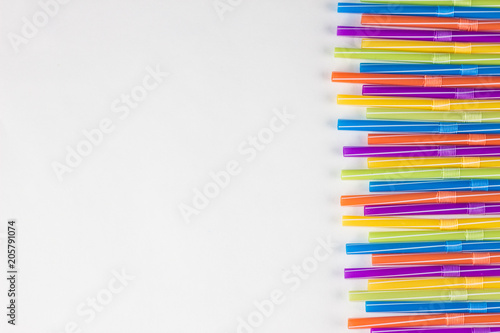 Poster  Multicolored strawberries for drinking on a white background, straw