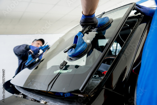 Automobile special workers replacing windscreen or windshield of a car in auto service station garage Tapéta, Fotótapéta