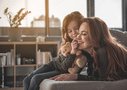 Fotobehang Wintersporten Portrait of smiling woman and child lying on sofa. Little girl is touching her mom nose with her finger holding teddy bear. Cute family is happy and looking perfect