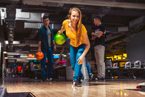 Leinwand Poster Young woman throwing bowling ball