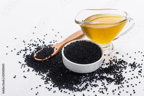 Fototapeta grains of black cumin and oil on the rustic background obraz