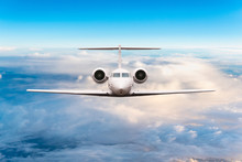 Front View Of Aircraft. Privat Jet In Flight. The Passenger Plane Flies High Above The Clouds And Blue Sky. Luxury Travel Concept