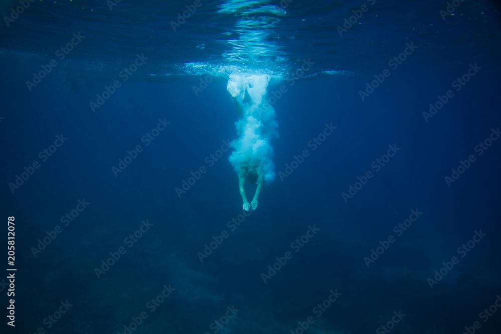 Fototapeta partial view of man diving into ocean