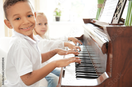 African-American boy with little girl playing piano indoors