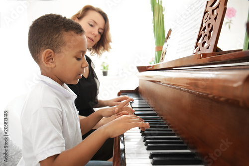 African-American boy with teacher learning to play piano indoors
