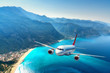 Leinwandbild Motiv Airplane is flying over amazing mountains with forest and sea at sunrise in summer. Landscape with white passenger airplane, sky, islands and blue water. Passenger aircraft. Travel and resort. Tourism