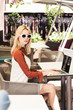 beautiful young woman in sunglasses using laptop