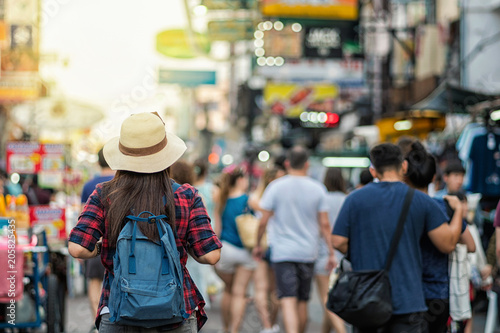 Spoed Fotobehang Japan Back side of Young Asian traveling women walking and looking in Khaosan Road walking street in evening at Bangkok, Thailand, traveler and tourist concept