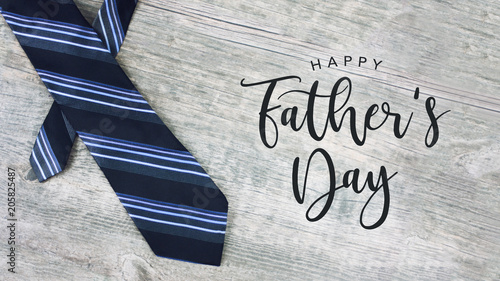 Happy Father's Day Text with Striped Tie Over Light Wood Background