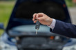 Selling a car, the seller gives the car keys to the buyer, buying a car, buying a new car with a smile