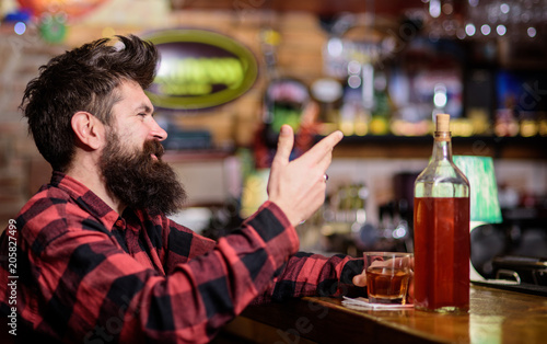 Poster de jardin Bar Hipster with beard ordered full bottle of alcohol. Relaxation concept. Man drinks whiskey or cognac. Man with happy face sits near bar counter. Guy spend leisure in bar, defocused background.