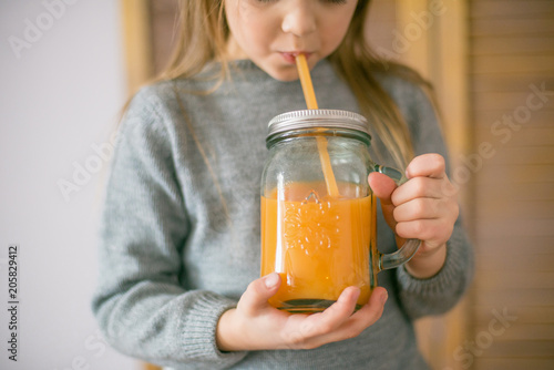 Foto op Canvas Sap Cute little girl with glass of orange juice at home, closeup