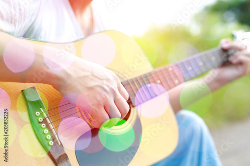 Colored bokeh image of male hand playing on acoustic guitar. Canvas-taulu