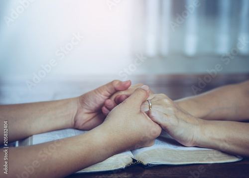 Fotografie, Obraz  Two people are praying together over holy bible on wooden table