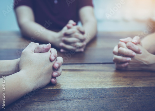 Christian bother and sister raise hands up and praying together around wooden table ,small prayer group in church, christian background with copy space for your text Fototapete