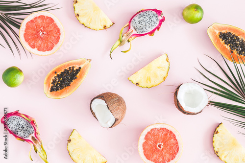 Poster Vruchten Summer fruits. Tropical palm leaves, pineapple, coconut, papaya, dragon fruit, orange on pastel pink background. Flat lay, top view
