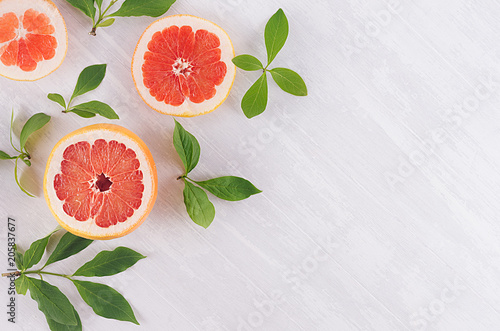 Slices grapefruit and green leaves on soft white wooden background, pattern, top view, closeup.