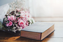 Bible And Flowers On Wooden Table Against Widow Light