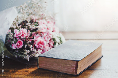 bible and flowers on wooden table against widow light Tablou Canvas