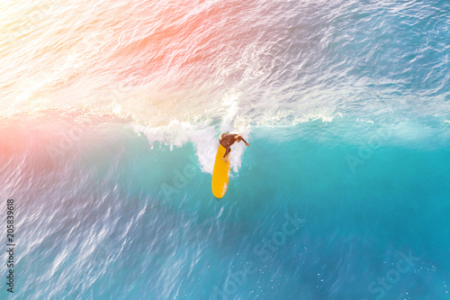 Surfer on a yellow surfboard in the ocean on a sunny day Wallpaper Mural