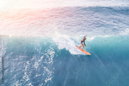 Surfer in the ocean on a sunny day, top view