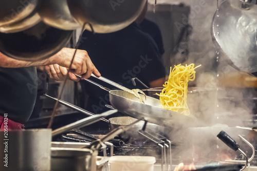 Stampa su Tela The cook prepares pasta in a restaurant