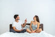The young couple sitting on the bed and gesturing