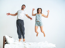 The Couple Jumping On The Bed On The White Background