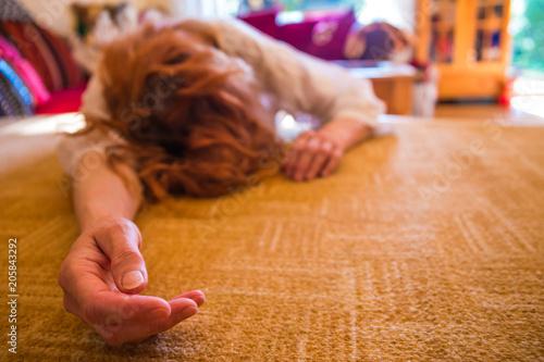 Obraz eine Frau liegt bewusstlos auf dem Teppich in einem Raum - fototapety do salonu
