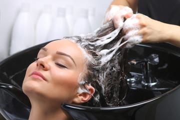 Fototapeta Hairdresser washing woman's hair in hairdresser salon