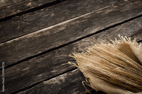 Fotografie, Obraz  Rye ears wrapped in burlap cloth on aged wooden table background with copy space
