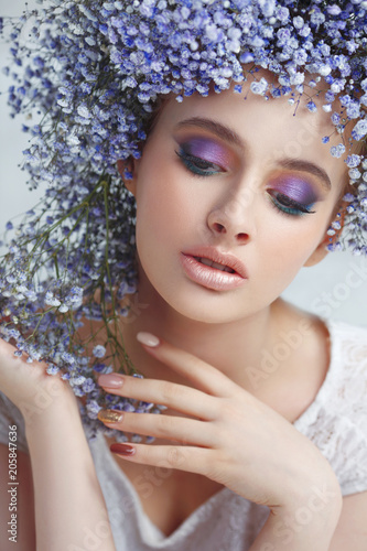 Fototapety, obrazy: Fashion beauty portrait of a beautiful girl in a voluminous wreath made of small blue flowers on a light background.