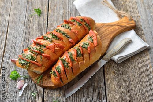 Foto op Plexiglas Buffet, Bar Überbackenes Baguette mit frischer Kräuterbutter und scharfer Chorizo Salami frisch aus dem Ofen serviert – Spanish snack: Baked bread with herb butter and hot Chorizo salami