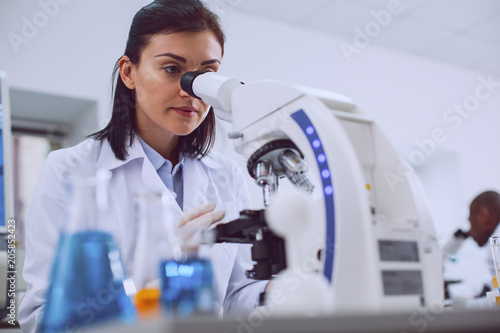 Challenging research. Determined experienced scientist working with her microscope and wearing a uniform